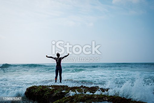 Woman surfer open arms to the sea waves at seaside