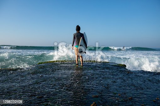 Woman surfer with surfboard going to surf at seaside
