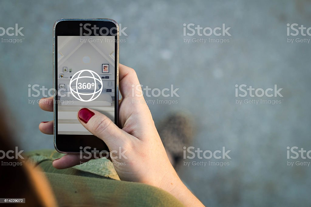 Woman surfing a 360 degree view in her smartphone stock photo