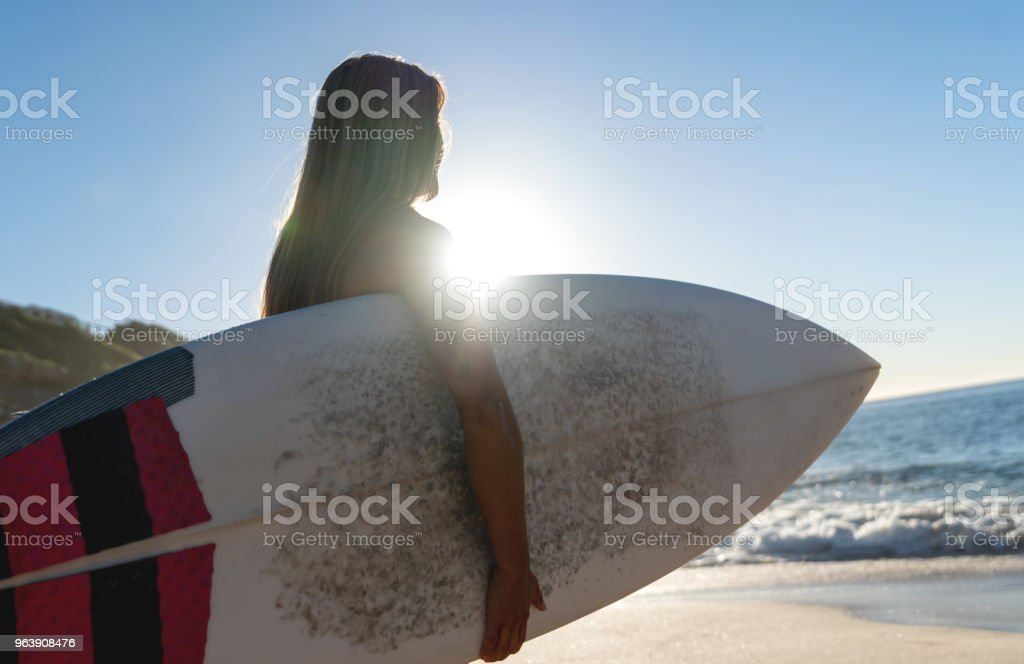 Woman surfing carrying her board and watching the sunrise - Royalty-free Adult Stock Photo