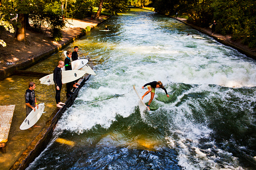 Woman surfing in the Eisbach river Munich Germany