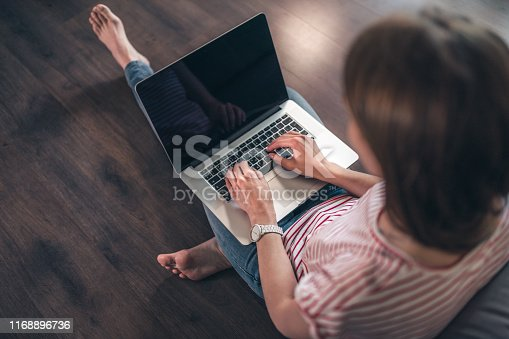 939030682 istock photo Woman surfs the web on a laptop at home 1168896736