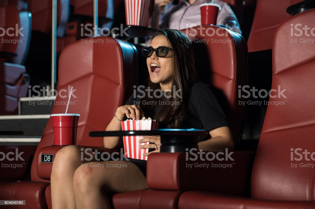 Woman surprised by a 3D scene at the movies stock photo