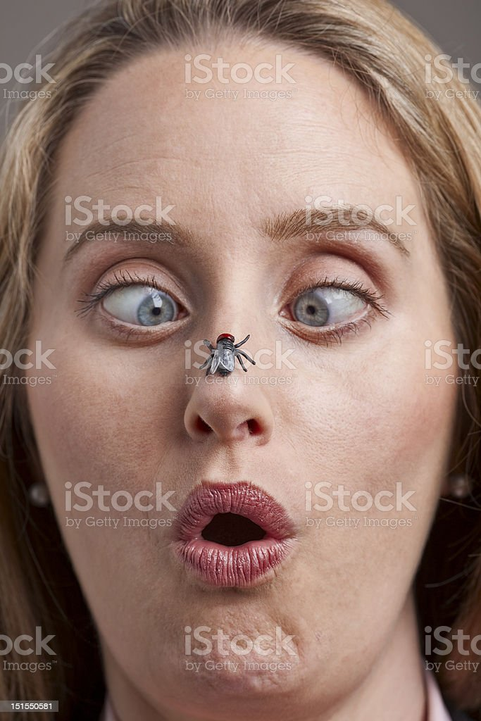 Woman surprised by fly on her nose stock photo
