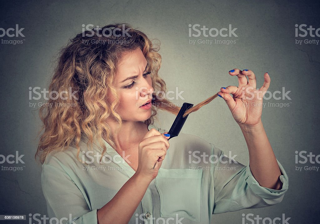 woman surprised she is losing hair has split ends stock photo