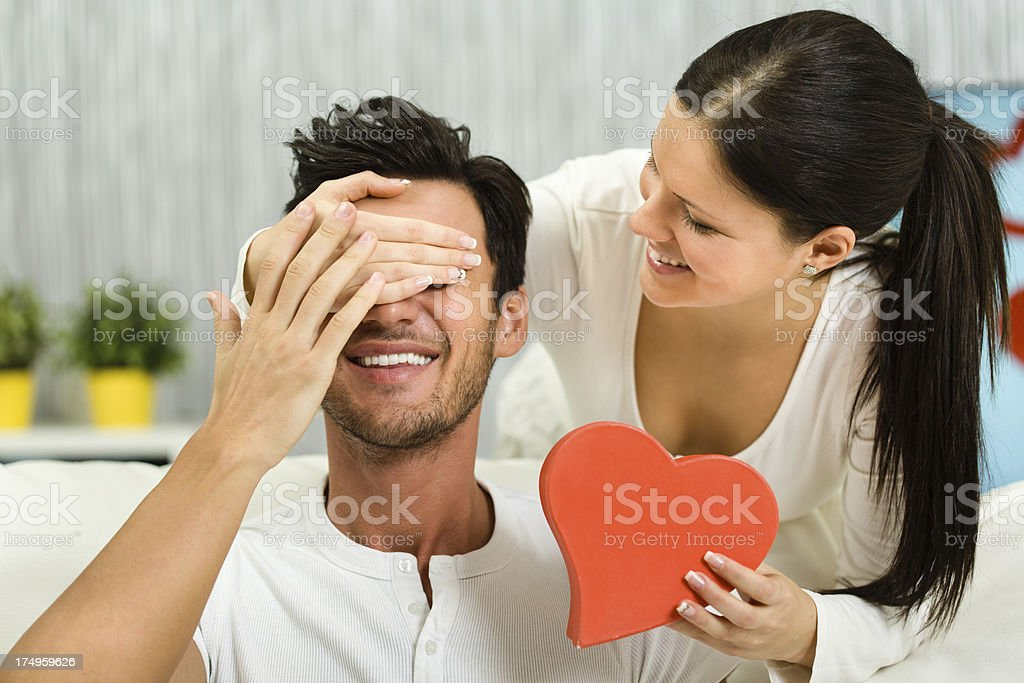 Woman surprising boyfriend with present royalty-free stock photo