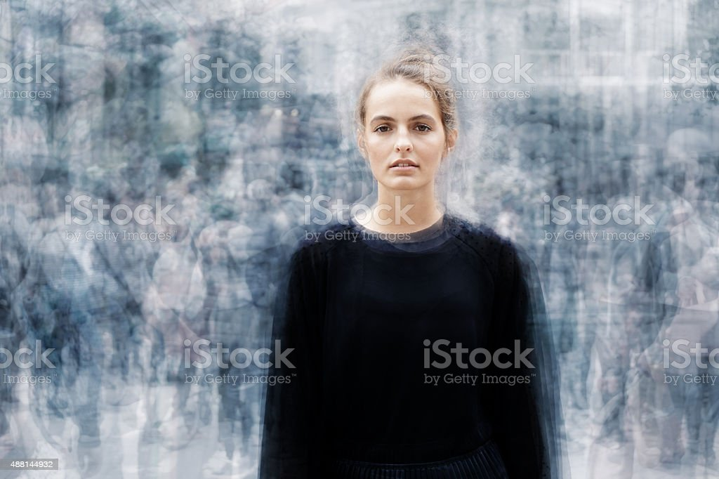 woman surrounded by a busy crowd of moving people stock photo
