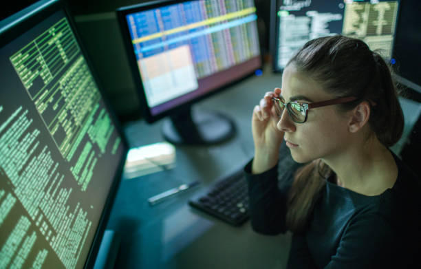Woman surrounded by monitors stock photo