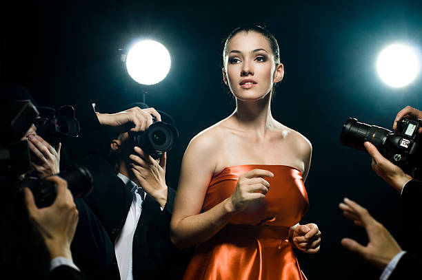 A woman surrounded by paparazzi Photographers are taking a picture of a film star diva human role stock pictures, royalty-free photos & images