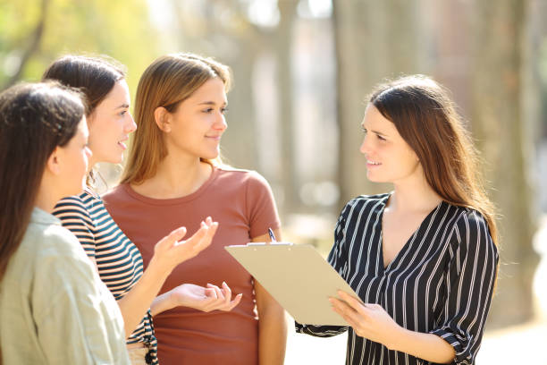 Woman surveying three people in the street stock photo