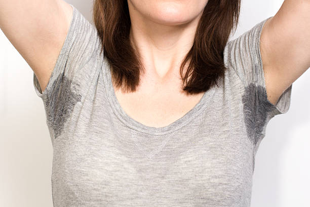 Woman sweating very badly under armpit Woman sweating very badly under armpit and holding nose wet clothing women t shirt stock pictures, royalty-free photos & images