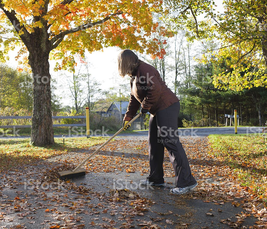 Woman Sweeping Fall Leaves. stock photo