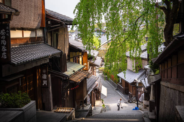 Woman sweeping path near stores in Higashiyama district in Kyoto, Japan stock photo