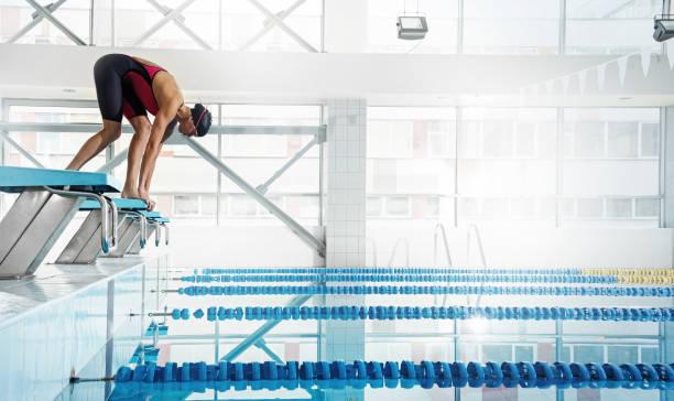 nageur de femme dans une position de départ - starting block photos et images de collection