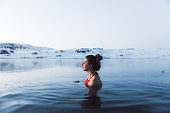 Young woman in red swimsuit bathing in picturesque hot swimming pool enjoying the view of snowy mountain peaks in North Iceland