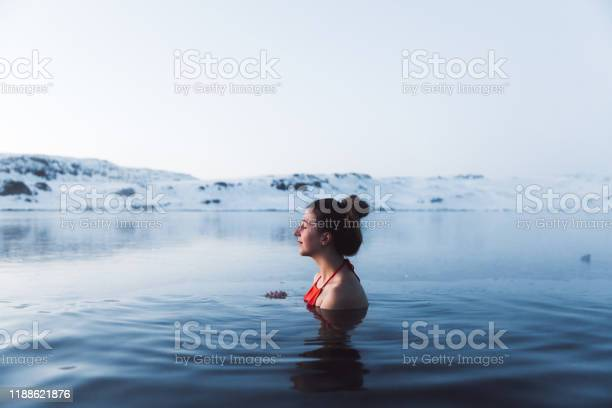 Photo of Woman swimming at the thermal pool with view of beautiful snowcapped mountains in Iceland