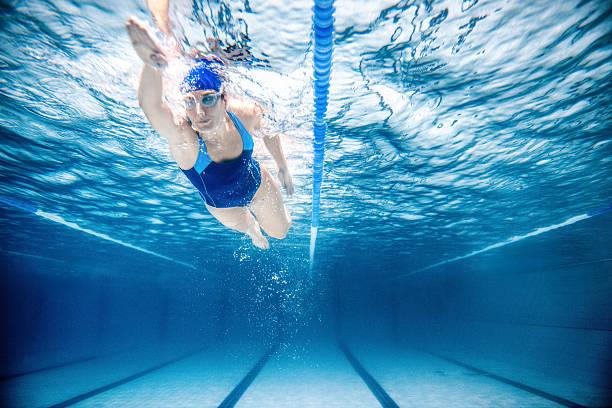 woman swimming freestyle - wedstrijdsport stockfoto's en -beelden