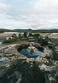 Young Caucasian woman  swimming  in hot pool in Iceland