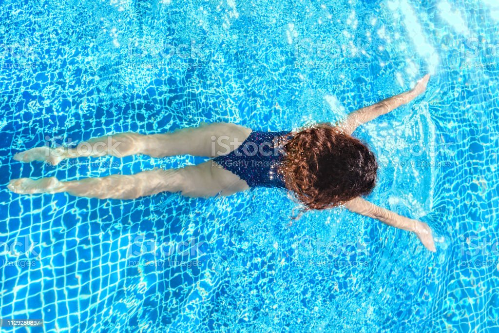 Woman swimming in pool. Top view. Straight body, slim. Breaststroke...