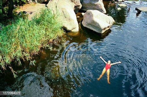 Young Caucasian woman swimming in river in summer. Camera film