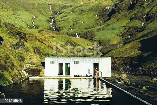 Young woman in red swimsuit going to swim in the old hot spring pool located in the middle of the beautiful green mountains in South Iceland