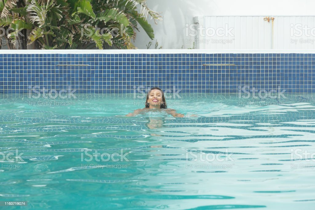 Front view of happy Caucasian woman swimming in swimming pool in the...