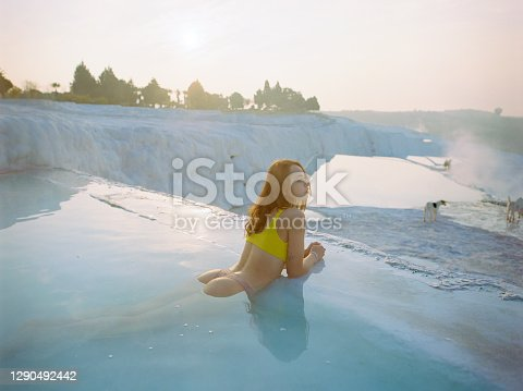 Young Caucasian woman swimming in travertine pool in Pamukkale