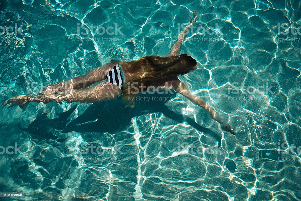 Woman swimming on a blue water pool stock photo
