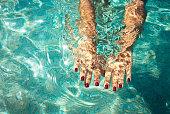 海で泳いでいる女性。澄んだ海の水の下で女性の手。