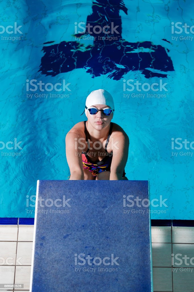 athletic woman in swimming hat and glasses ready to start swimming...