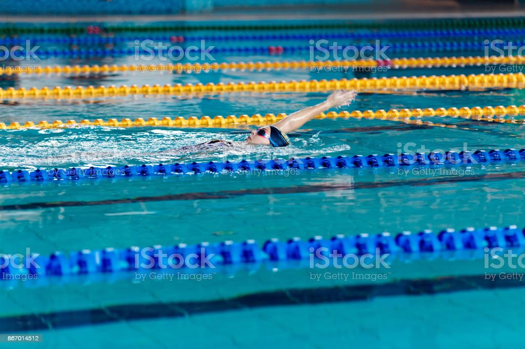 athletic woman swimming with swimming hat and glasses in swimming pool