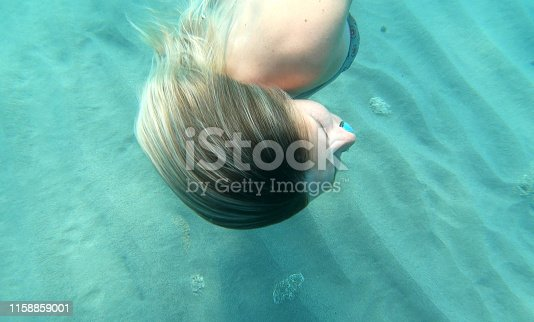 Underwater view of young woman swimming along sea floor