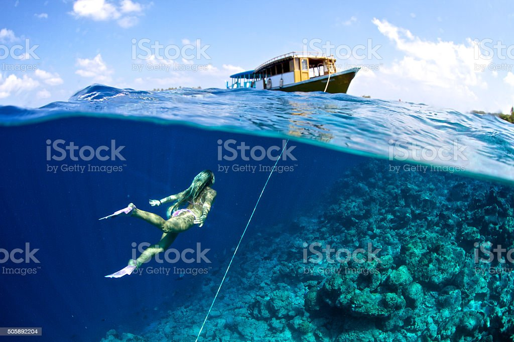Woman swims towards boat from the anchor stock photo