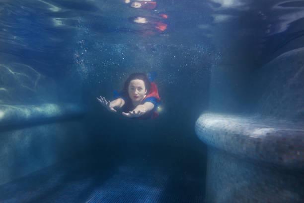 woman swims under the water like a mermaid. - frau tiefer ausschnitt stock-fotos und bilder