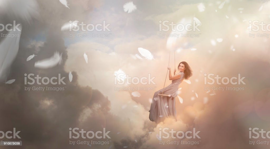 Woman swinging in sky with falling feathers stock photo
