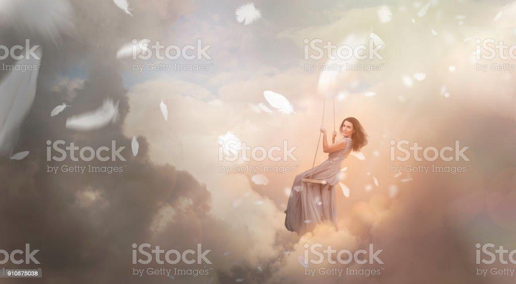 Femme se balançant dans le ciel avec des chutes de plumes - Photo