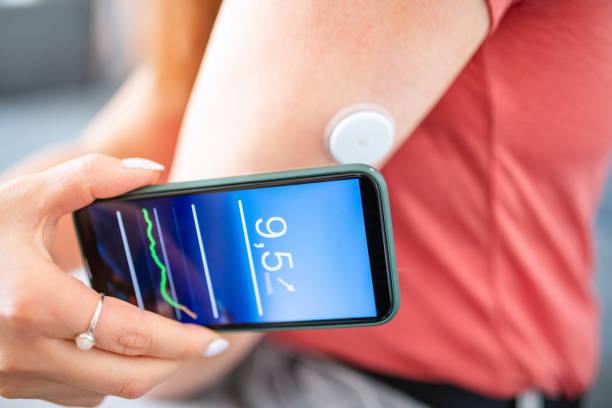 woman swiping glucose sensor with phone for measurement - medical technology стоковые фото и изображения