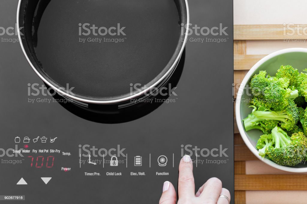 Woman switch on Induction stove stock photo