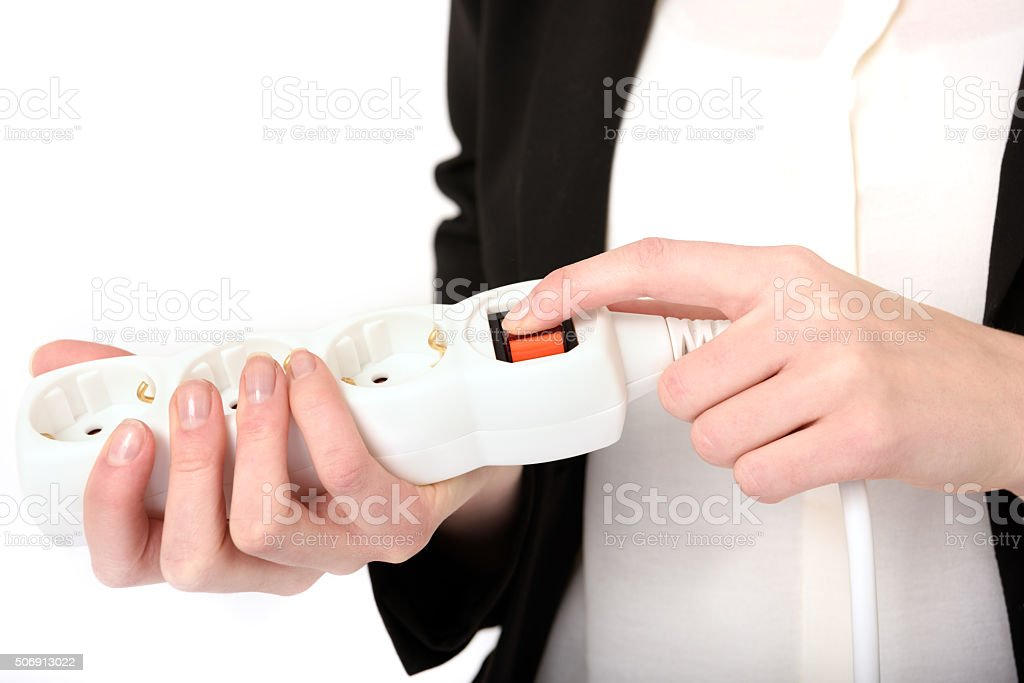 Woman switching on / off extension outlet stock photo
