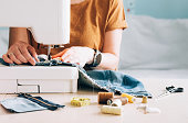 istock A woman tailor works at sewing machine sews reuses fabric from old denim clothes 1301201223