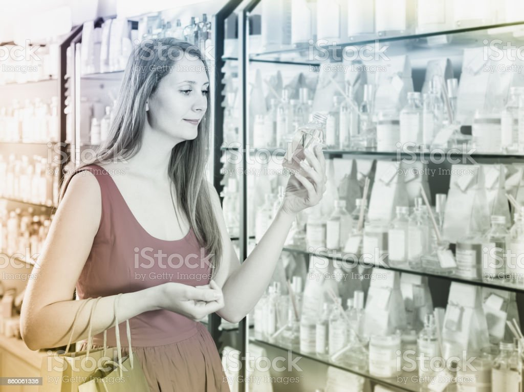 happy russian woman take a choise fresh perfume in perfume supermarket