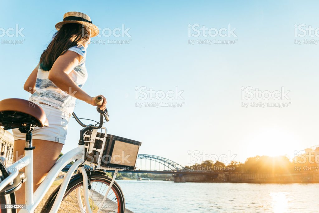 woman take a rest at embankment of the river and looking on sunset stock photo