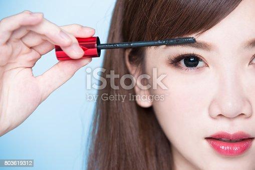 istock woman take mascara 803619312
