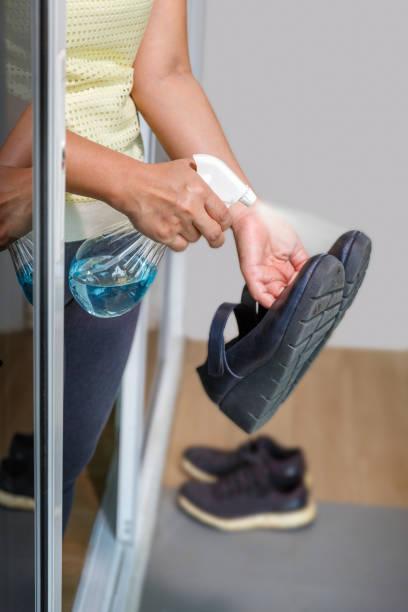 Frau ziehen ihre Schuhe aus und reinigen mit Alkohol, bevor sie ein Haus zum Schutz infiziert von Covid-19 – Foto