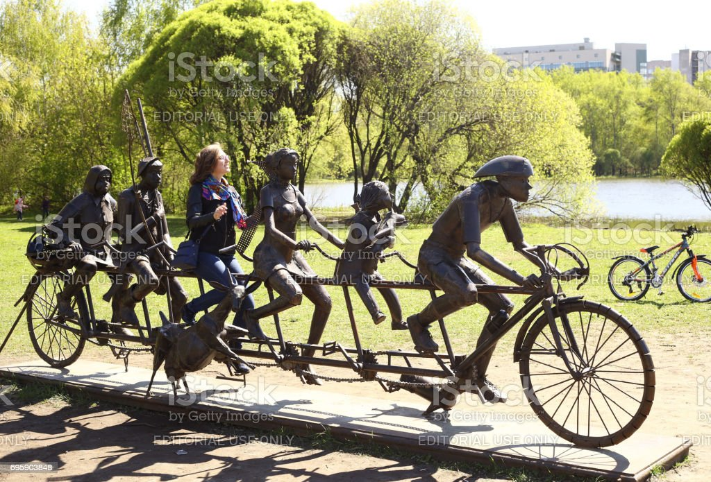 woman take picture in cycling people sculpture in city park stock photo
