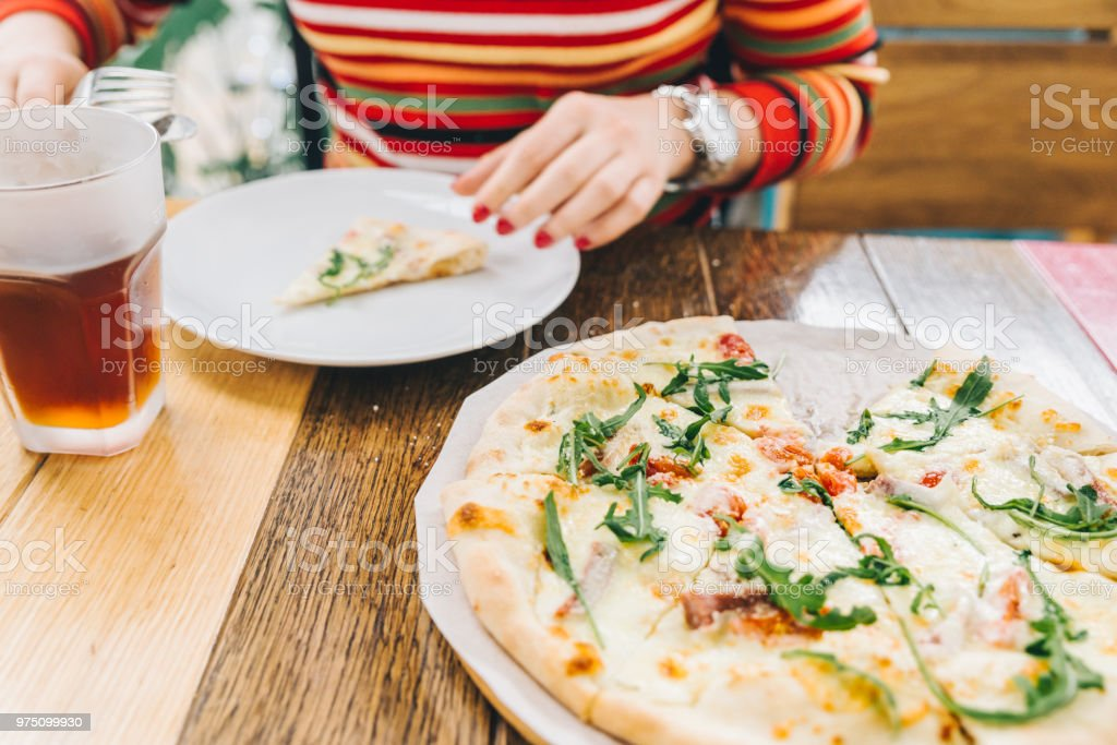 woman take piece of pizza close up. soft focus stock photo