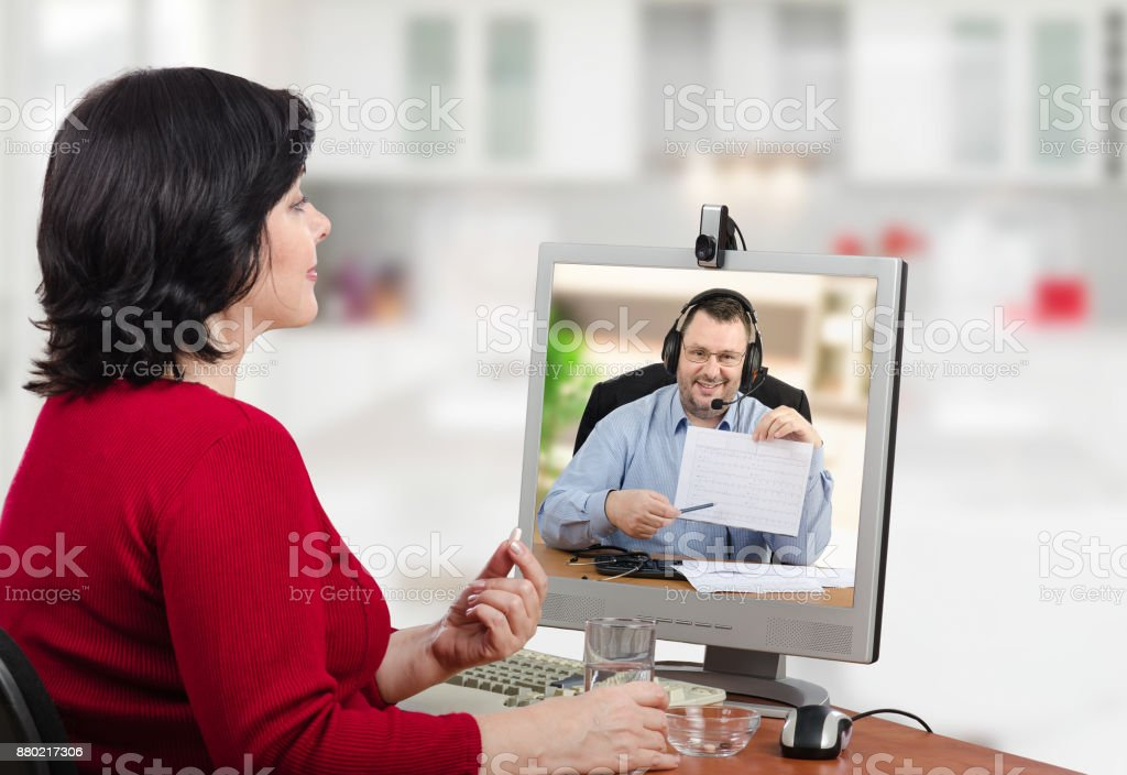 Woman takes a pill during virtual doctor appointment stock photo