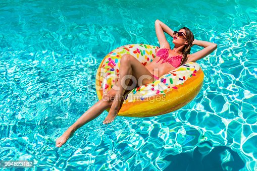 Beautiful, young woman takes a sunbath in a donut shaped pool float on a hot summer day