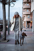 A woman takes a walk with her dog down the street one winter day