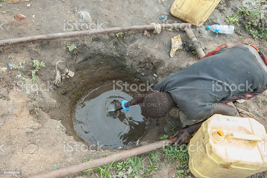 Woman takes drinking water in refugee camp, Juba, South Sudan. stock photo